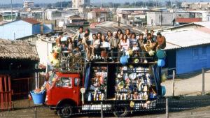 Pakettiauto, jossa on tavaraa ja iso joukko ihmisiä katolla.