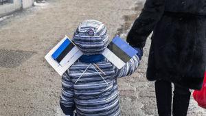En liten pojke som har två Estlandsflaggor instuckna under halsduken.