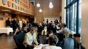 en massa människor i finare klädsel sitter i en aula och äter tårta och dricker kaffe