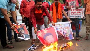 Män bränner bilder på den kinesiska presidenten Xi Jinping.