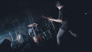 Två musiker som spelar trummor och gitarr.