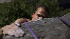 En man klättrar upp för en vägg. Man ser bara halva hans ansikte ovanför bergsklacken och en hand som greppar tag om den.