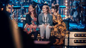 Kolme naista istuvat SuomiLOVEn lavan reunalla nauraen.