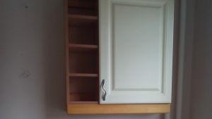 Ett vitt köksskåp med träskiva.