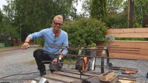 En man med en metallkonstruktion