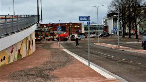 Uppfarten på en bro intill en stenbelagd gata och några skyltar för bussar.