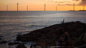 vindmöllor syns i en solnedgångshorisont vid havet. Några människor går på några klippor vid havet.
