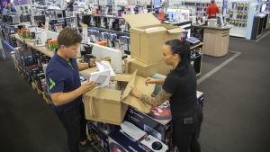 Två försäljare i en elektronikaffär packar upp kartonglådor mitt inne i affären. Hyllor med hemelektronik syns i bakgrunden.