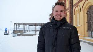 Porträttfoto av ung man med skägg och svart dunjacka tagen utomhus vintertid.