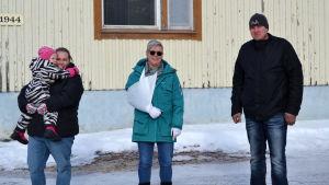 Tre personer, varav den ena håller ett barn i famnen, står och tittar in i kameran. Gammal träbyggnad i bakgrunden som är beigemålad. Det är vinter och snö.
