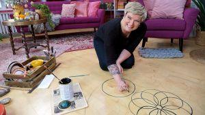 Iloinen nainen piirtää lattialla.