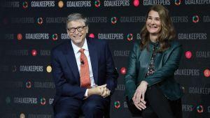 Leende Bill och Melinda Gates poserar sittande framför reklamvägg som marknadsför en av deras evenemang.