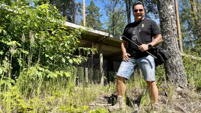 En man i t-skjorta och shorts poserar med en ormkrok i handen framför ett litet hus.