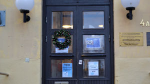 En gammal dubbeldörr på ett stenhus. Dörrens fönster pryds av olika affischer och en julkrans.