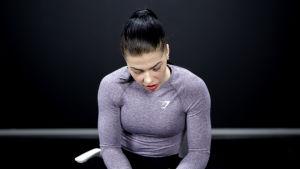 Fitness-urheilija Pernilla Böckerman istuu mietteliäänä katse lattiaan päin valokuvausstudiossa.