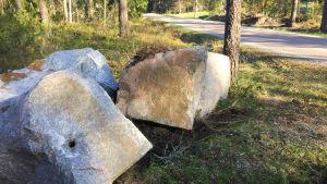 Tre jättestora stenblock ligger vid vägkanten vid en asfalterad väg i skogen.