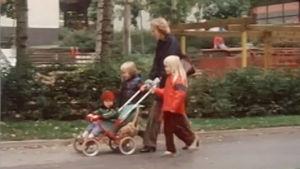 Äiti työntää lastenrattaita vieressään kaksi lasta