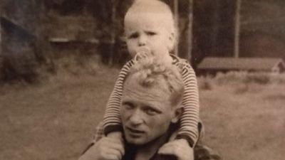 Ett svartvitt fotografi på en man som bär en pojke på sina axlar.