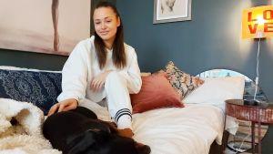 Kiara Nelson på säng med hund. Tavlor på väggen