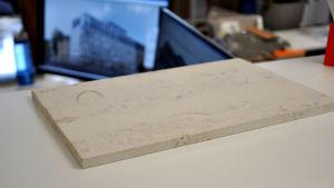En gråvit lite spräcklig stenplatta på en bordsyta - plattan är ett par centimeter tjock och cirka 40x20 centimeter stor.