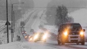 Bilar med lyktorna påslagna kör på en landsväg i snöväder.