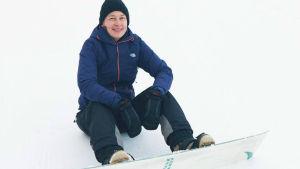 kaisa leka sitter i backen med snowboard