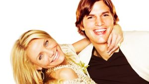 Cameron Diaz roikkuu Ashton Kutcherin kaulasta, molemmat hymyilevät leveästi ja katsovat kameraan.