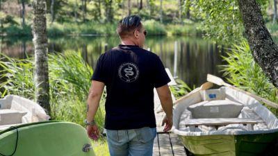 En man går på en brygga mellan några båtar mot en sjö.