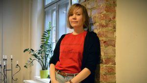 Ylva Perera, i en röd t-shirt, lutar sig mot en tegelvägg.