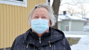 Birgitta Lindén utomhus framför en gul byggnad med munskydd på.