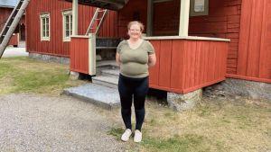 Lilian Pettersson-Smeds med ett rött hus i bakgrunden.