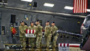 Sotilaat kantavat Yhdysvaltain lipulla peitettyä arkkua.