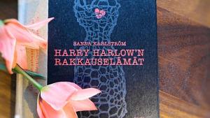 Sanna Karlströmin teos Harry Harlow'n rakkauselämät pöydällä vaaleanpunaisten tulppaanien vieressä
