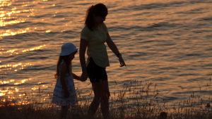 kvinna och liten flicka går på stranden i kvällssolen