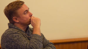 en man sitter i profil och funderar