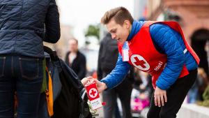 en ung man med insamlingsbössa för hungerdagsinsamlingen