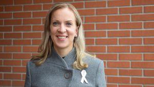 En leende Sandra Bergqvist iklädd grå rock ståendes framför en röd tegelvägg.