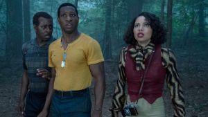 Två män och en kvinna står i en skog i skymningen och tittar skrämt upp mot trädtopparna.