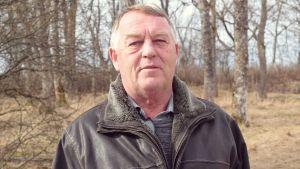 Greger Lindholm med ett vårigt, men grått parklandskap i bakgrunden.