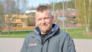 Matti Pelander i grå jacka på en sandplan.