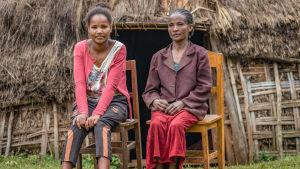 Nuori ja vanhempi etiopialainen nainen istuvat kotinsa edessä puutuoleilla.