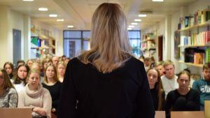 Sandra bergqvist med ryggen till kameran står framför en gymnasieklass och talar.