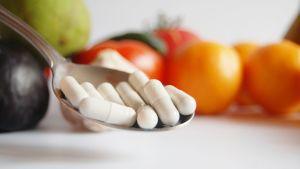 Lusikassa valkoisia pillereitä joiden taustalla vihanneksia.