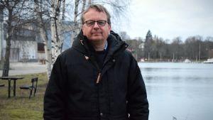 Sam Forsblom i en svart rock på Valsverksholmen framför Dalsbruks hamn.