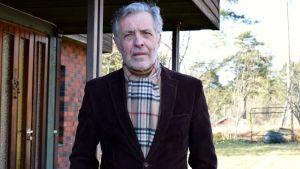 Jan-Erik Enestam i brun tweed-kavaj utanför ett tegelhus.