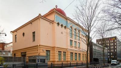 Gatuvy över Helsingfors synagoga - ett gult hus i klassisk stil, ett rött kupoltak skymtas där ett tak ska vara.
