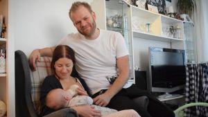 Heidi och Nikolai Sumelius sitter i en fotölj i vardagsrummet. Heidi matar deras spädbarn i famnen.