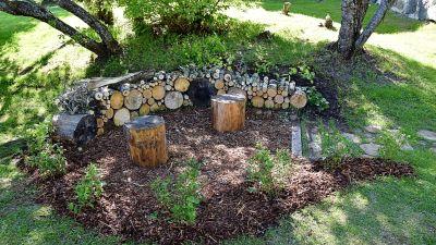 Cirkelformat trädgårdsrum med låg mur av ved och häck av buskblåbär