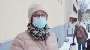 Christine Huusko framför en gul vägg med munskydd på.