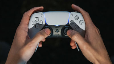 Playstation 5 pelikonsolin ohjain pelaajan käsissä.